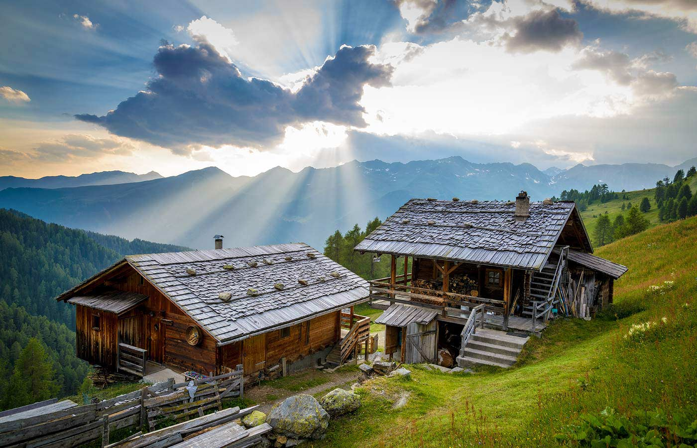 Two old wooden alpine huts illuminated by the light of the sun hidden by the clouds