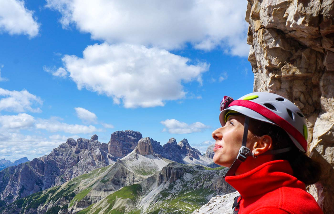 Close-up of girl's face with a hiker helmet admiring the view of the Alps in South Tyrol