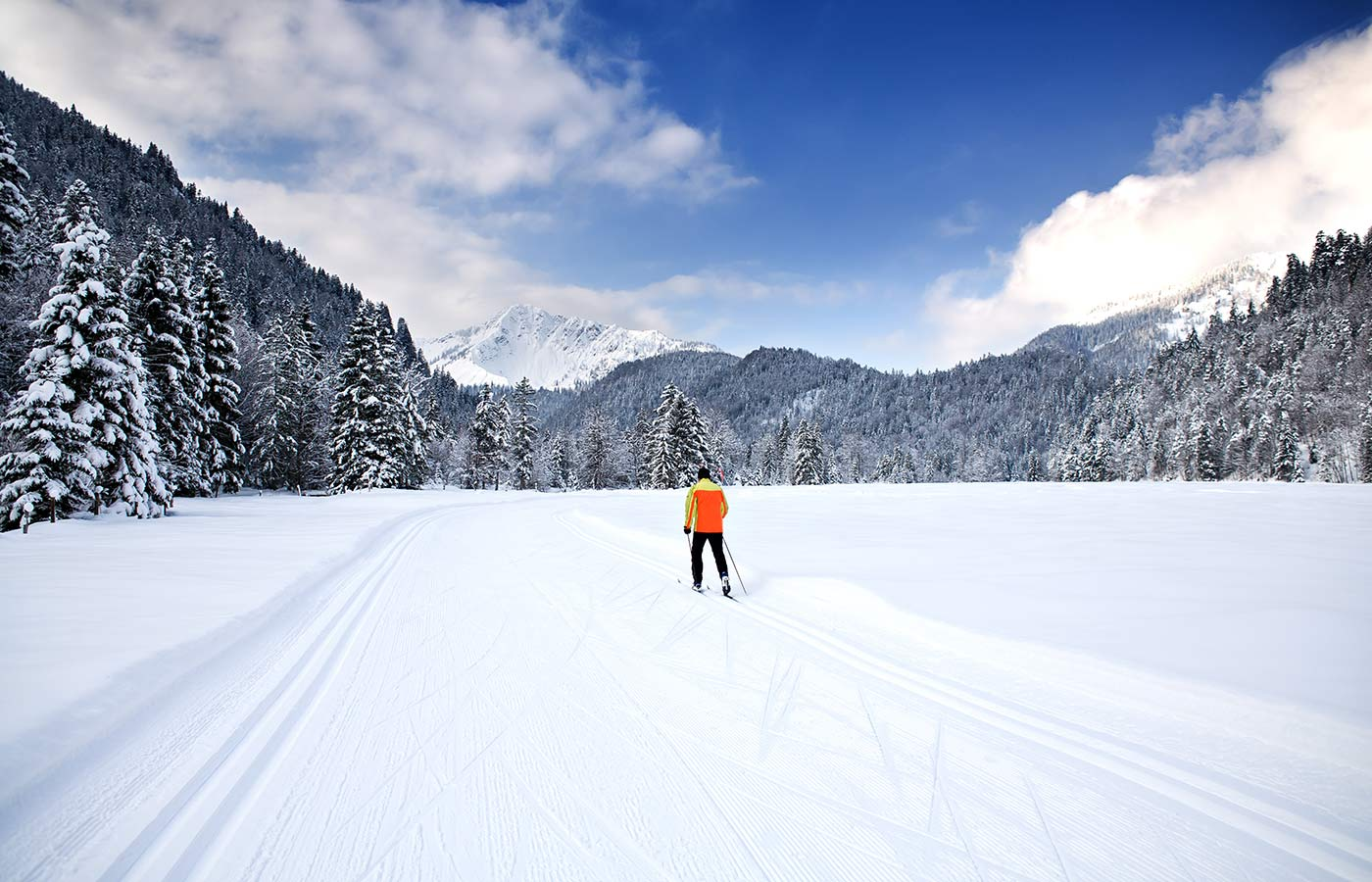 A cross-country skier along a track on a snowy mountain valley