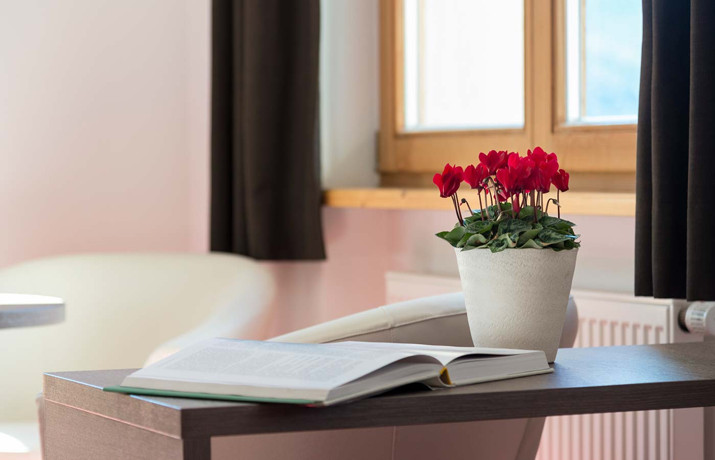 Vase of flowers and book open on a table in one of the rooms at the Waldheim's