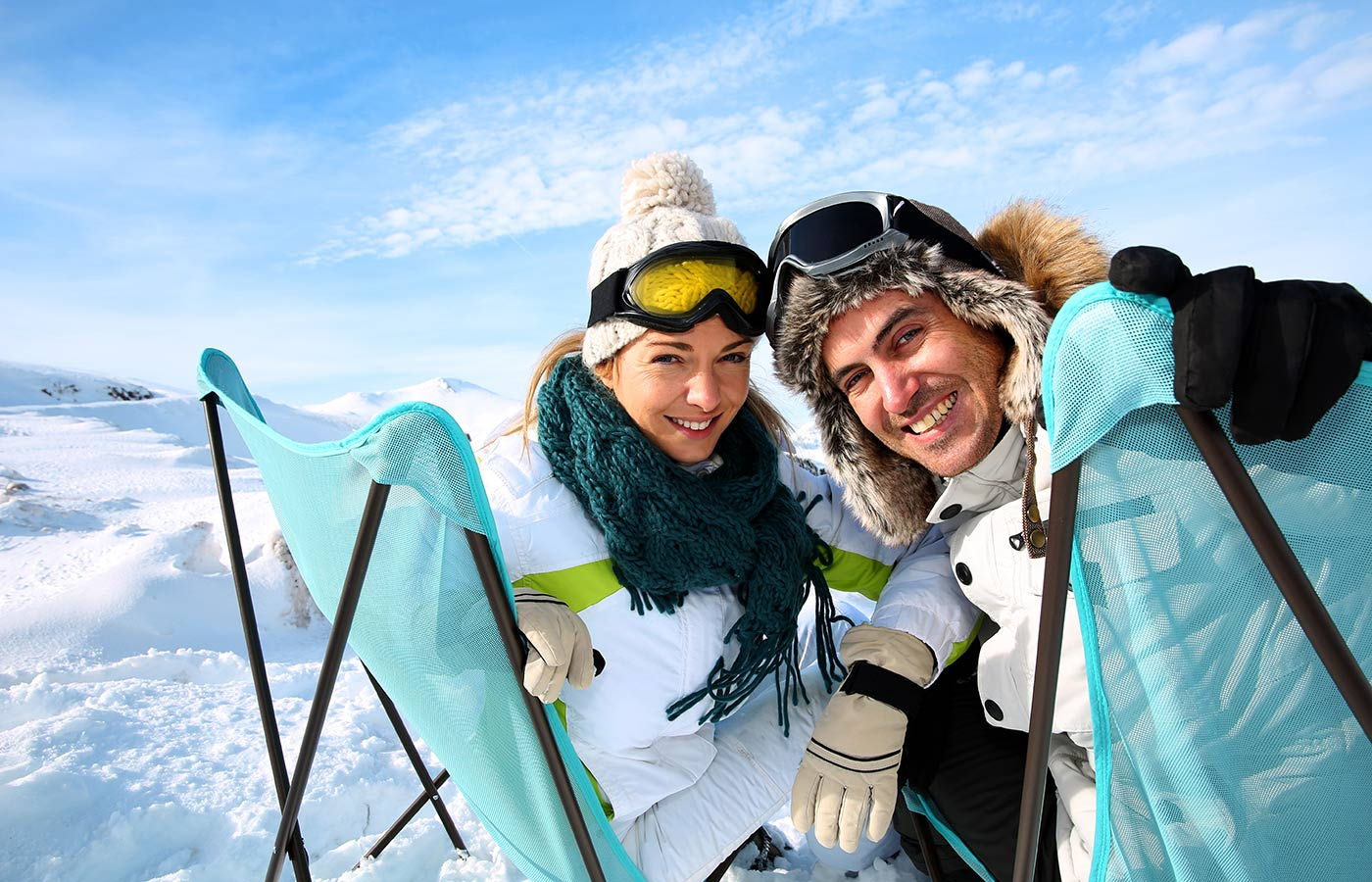 Young smiling couple with snow equipment enjoying the mountain sun on two decks in the snow