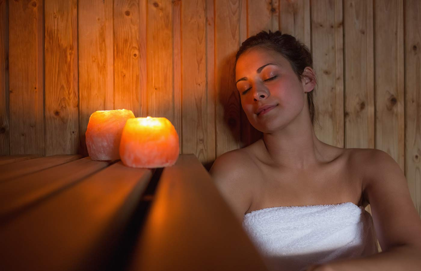 Girl relaxing in a sauna with her eyes closed by candlelight