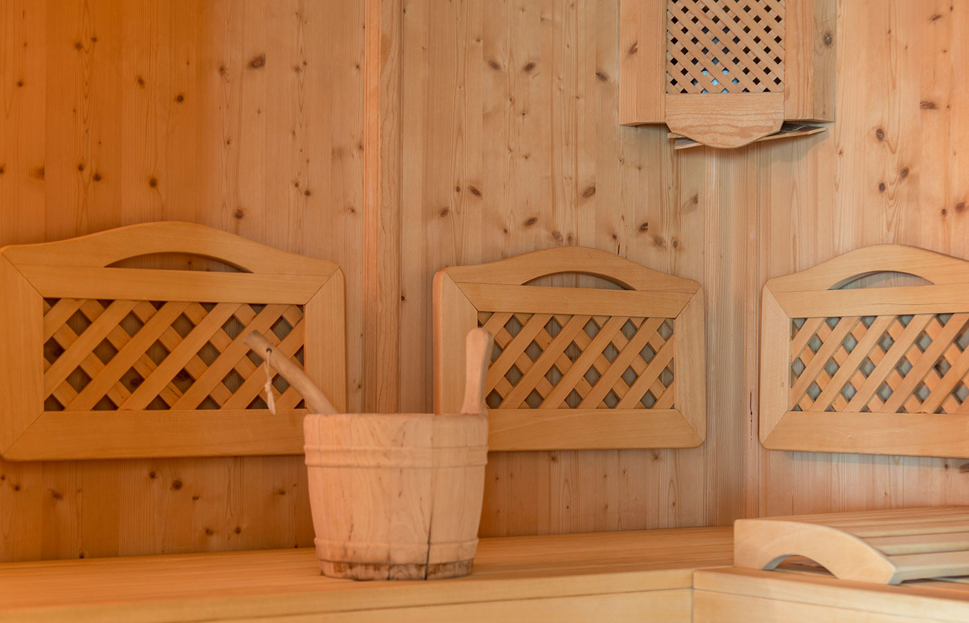 Sitting and walls in natural wood inside the sauna of Hotel Waldheim in South Tyrol