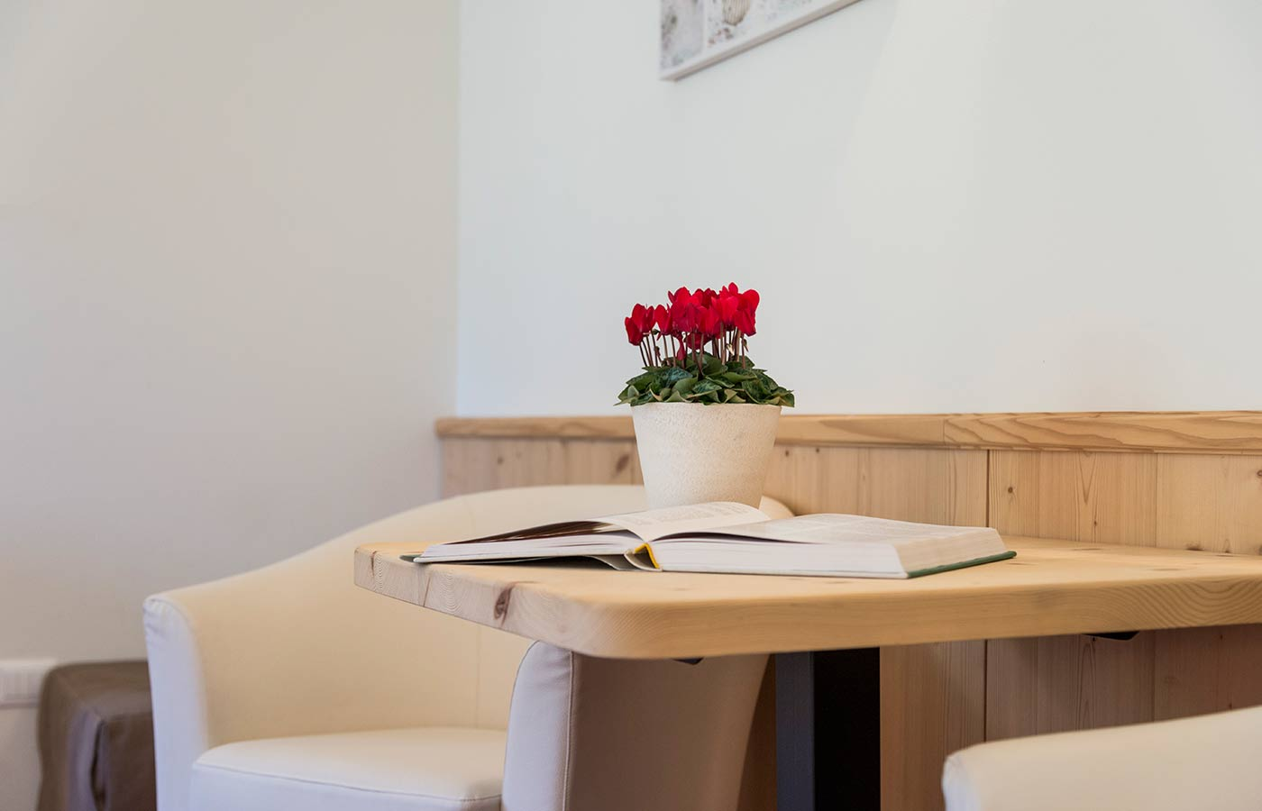 Wooden table with vase of flowers and open book in the room of Hotel Waldheim