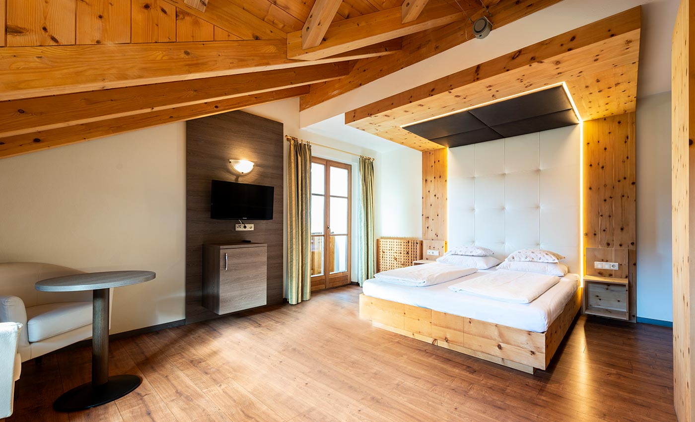Double bed by natural wood in a room of the Hotel Waldheim in South Tyrol, Italy